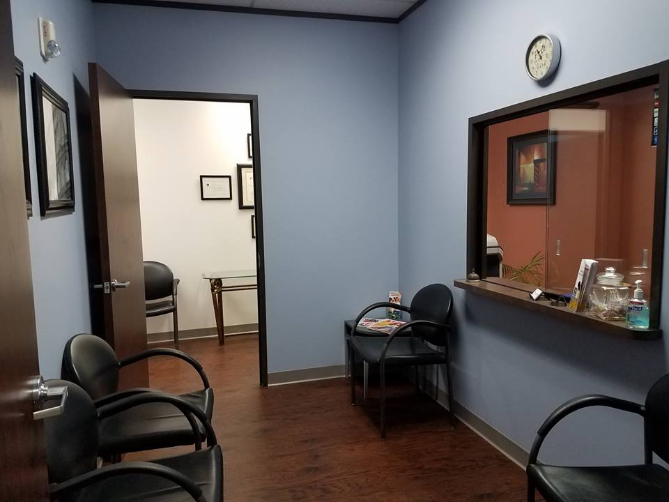 The entryway of Synergy Chiropractic of Houston. The waiting room leads to the main hallway, while the office assistant's office is to the right behind the glass window.